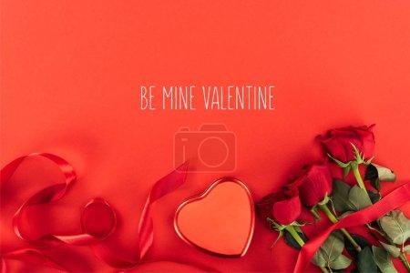 """Photo pour Vue du haut de la boîte en forme de coeur et des roses isolées sur rouge avec lettrage """"be mine valentine"""", concept de Saint Valentin - image libre de droit"""