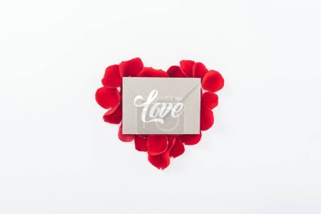 """Photo for Top view of envelope with """"sending you love"""" lettering and heart made of red rose petals isolated on white, st valentines day concept - Royalty Free Image"""