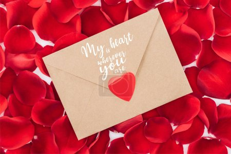 "Photo for Top view of envelope with ""my heart is wherever you are"" lettering, heart and red rose petals on background, st valentines day concept - Royalty Free Image"