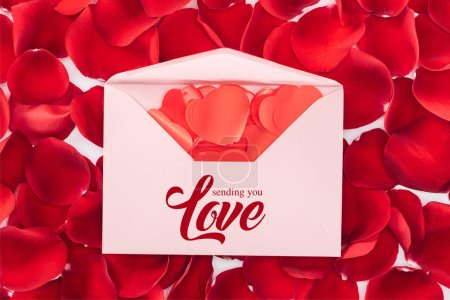 "Photo for Top view of envelope with ""sending you love"" lettering, heart shaped confetti and red rose petals on background, st valentines day concept - Royalty Free Image"