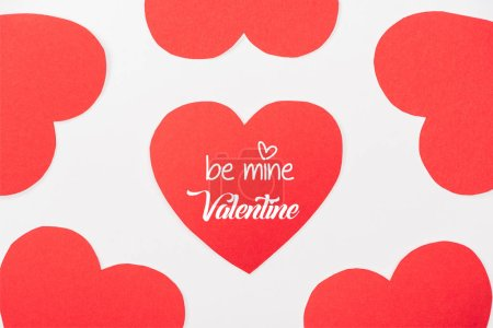 "Photo for Background with heart shaped paper cards isolated on white with ""be mine valentine"" lettering - Royalty Free Image"