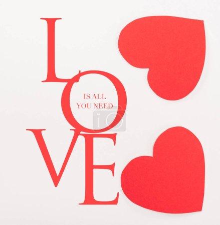Photo pour Top vue sur coeur rouge en forme de cartes en papier isolés sur blanc avec «Love is all you need» lettrage, st Valentin concept - image libre de droit
