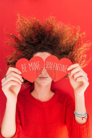 """Photo for Top view of girl holding heart shaped cards with """"be mine valentine"""" lettering in front of face isolated on red, st valentines day concept - Royalty Free Image"""