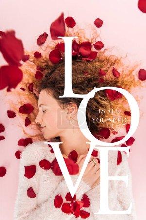 """Photo pour Vue du dessus de la belle fille et des pétales de rose tombants isolés sur rose avec le lettrage """"L'amour est tout ce dont vous avez besoin"""" - image libre de droit"""