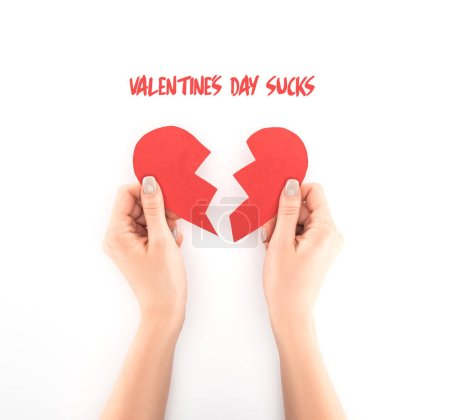 "cropped shot of woman holding red heart symbol isolated on white, with ""valentines day sucks"" lettering"