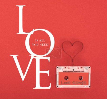 Photo pour Élevé vue sur cassette audio contenant les chansons d'amour de lettrage et symbole du coeur faite de bandes isolées sur rouge, st Valentin jour concept avec «Love is all you need» lettrage - image libre de droit