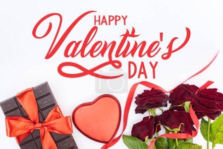 Foto de Vista superior de chocolate envuelto por la fiesta de la cinta, rosas rojas y caja de regalo en forma de corazón aislado en blanco, feliz día de San Valentín - Imagen libre de derechos