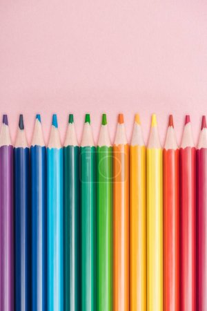 Photo for Rainbow multicolored pencils arranged in horizontal line on pink background, lgbt concept - Royalty Free Image