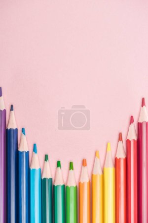 top view of rainbow multicolored pencils on pink background, lgbt concept