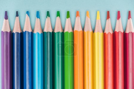 Photo for Top view of rainbow multicolored pencils arranged in horizontal line on blue background, lgbt concept - Royalty Free Image
