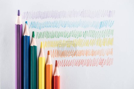 Photo for Top view of rainbow multicolored pencils and strokes on grey background, lgbt concept - Royalty Free Image
