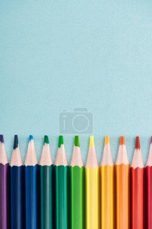 Regenbogen-Buntstifte in horizontaler Linie auf blauem Hintergrund angeordnet, lgbt-Konzept