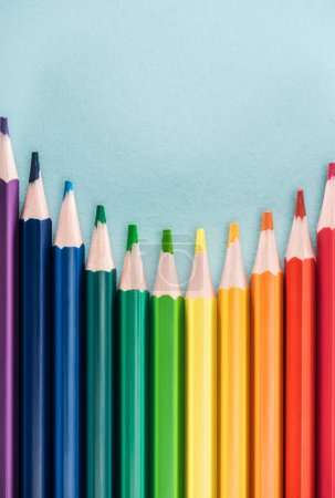 Photo for Top view of rainbow multicolored pencils on blue background, lgbt concept - Royalty Free Image