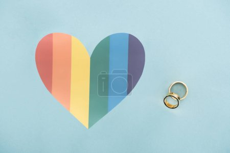 Photo for Wedding rings on blue background with rainbow colored heart, lgbt concept - Royalty Free Image