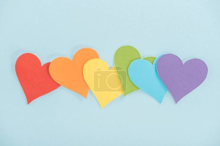 Photo for Rainbow colored paper hearts on blue background, lgbt concept - Royalty Free Image