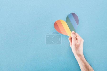 Photo pour Vue recadrée de la main masculine avec coeur en papier de couleur arc-en-ciel sur fond bleu, concept lgbt - image libre de droit