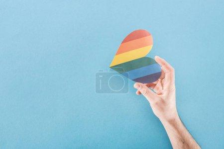 Photo pour Vue partielle de la main masculine avec coeur en papier de couleur arc-en-ciel sur fond bleu, concept lgbt - image libre de droit
