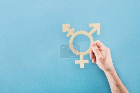 Photo pour Vue recadrée de la main masculine avec du papier blanc coupé signe de genre sur fond bleu, concept lgbt - image libre de droit