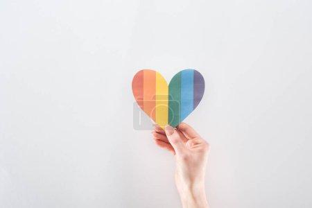 Photo pour Vue partielle de la main féminine avec arc-en-ciel de couleur coeur de papier sur fond gris, notion de lgbt - image libre de droit