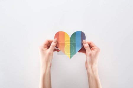 Photo for Partial view of woman holding rainbow colored paper heart on grey background, lgbt concept - Royalty Free Image