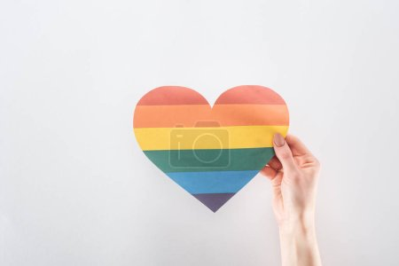 Photo pour Vue recadrée de la main féminine avec coeur en papier de couleur arc-en-ciel isolé sur gris, concept lgbt - image libre de droit