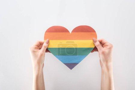 Photo pour Vue recadrée des mains féminines avec coeur en papier de couleur arc-en-ciel isolé sur gris, concept lgbt - image libre de droit