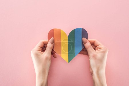 Photo for Cropped view of woman holding rainbow colored paper heart on pink background, lgbt concept - Royalty Free Image