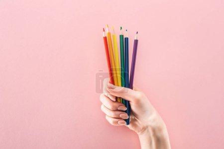 Photo pour Vue partielle de la main féminine avec rainbow crayons sur fond rose, concept lgbt de couleur - image libre de droit
