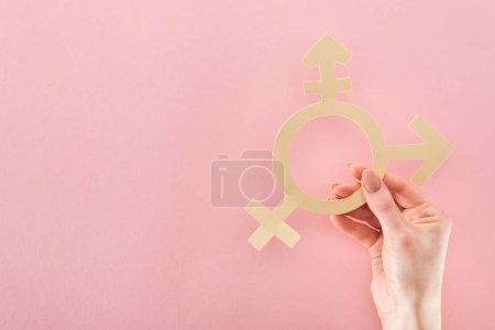 Photo pour Vue partielle de la main féminine avec papier coupé signe de genre sur fond rose, concept lgbt - image libre de droit