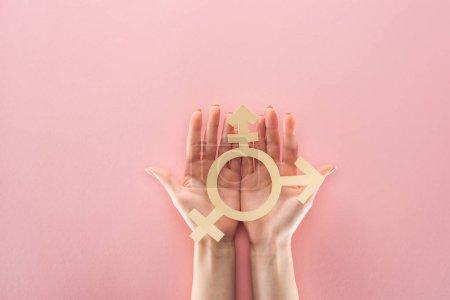 Photo pour Vue partielle des mains féminines avec papier coupé signe de genre sur fond rose, concept lgbt - image libre de droit