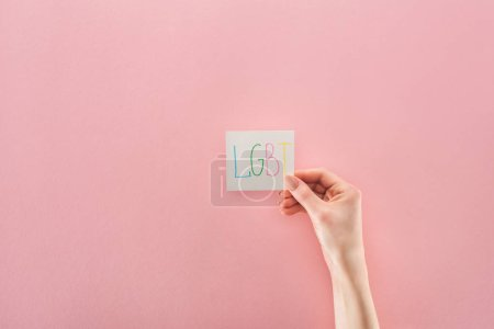 "partial view of female hand with ""lgbt"" handwritten abbreviation on white card on pink background"