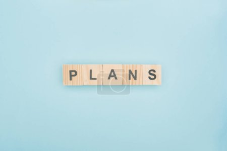 Photo for Top view of plans lettering made of wooden blocks on blue background - Royalty Free Image