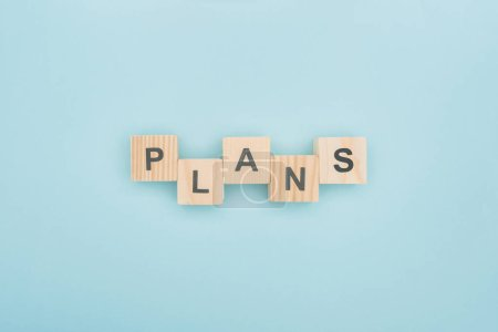 Photo for Top view of plans lettering arranged of wooden cubes on blue background - Royalty Free Image