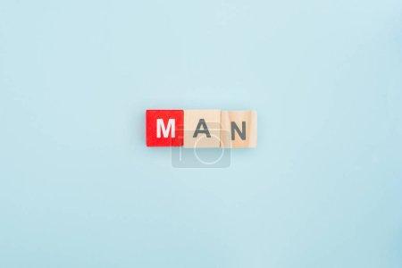 Photo pour Vue du dessus du lettrage homme en blocs de bois sur fond bleu - image libre de droit