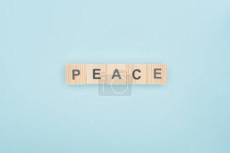 Photo pour Vue de dessus du lettrage paix faite de cubes en bois sur fond bleu - image libre de droit