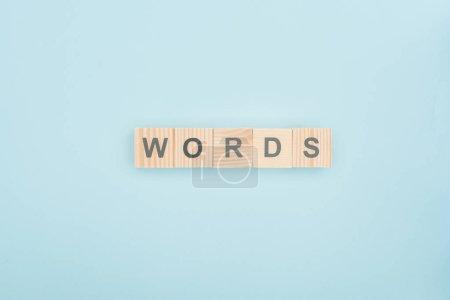 Photo pour Vue du dessus des mots lettrage en cubes de bois sur fond bleu - image libre de droit
