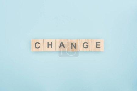 Photo pour Vue de dessus du lettrage changement constitué de blocs en bois sur fond bleu - image libre de droit
