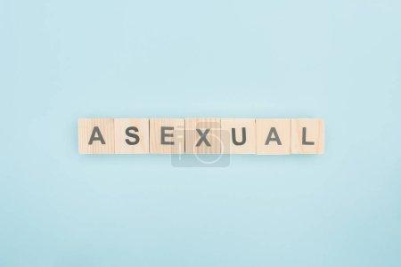 Photo pour Vue de dessus du lettrage asexuée faite de cubes en bois sur fond bleu - image libre de droit