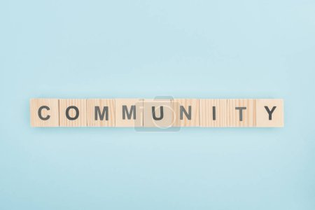top view of community lettering made of wooden cubes on blue background