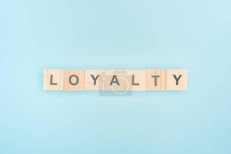 Photo pour Vue de dessus du lettrage de fidélité faite des cubes en bois sur fond bleu - image libre de droit