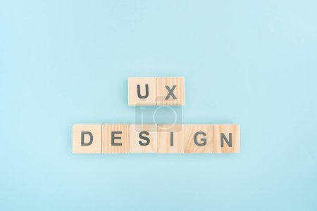 top view of ux design lettering made of wooden cubes on blue background