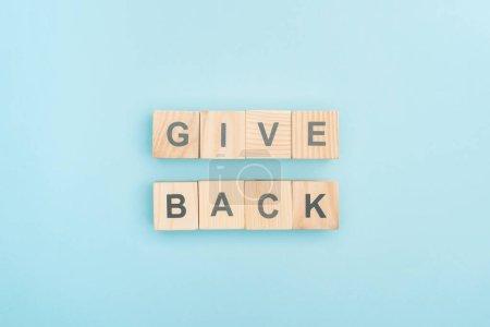 Photo pour Vue du dessus de donner retour lettrage en cubes de bois sur fond bleu - image libre de droit