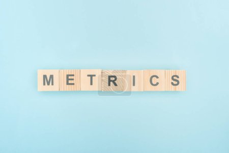 Photo for Top view of metrics lettering made of wooden cubes on blue background - Royalty Free Image