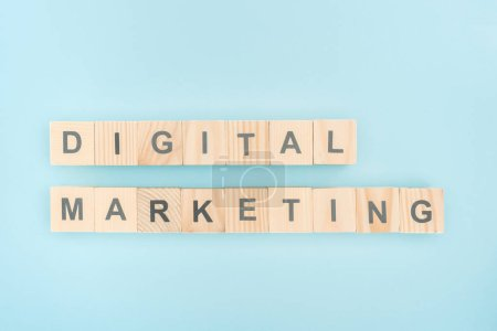 top view of digital marketing lettering made of wooden cubes on blue background