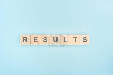 Photo pour Vue du dessus des résultats lettrage en cubes de bois sur fond bleu - image libre de droit