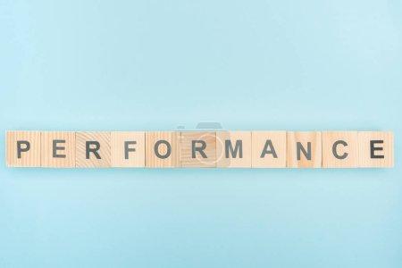 Draufsicht auf Performans Schriftzug aus Holzwürfeln auf blauem Hintergrund