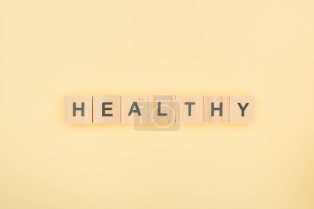 Photo pour Vue du dessus de lettrage sain en cubes de bois sur fond jaune - image libre de droit