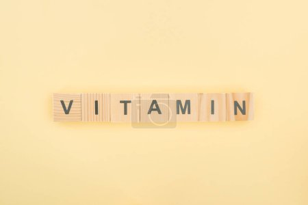 Photo for Top view of vitamin lettering made of wooden cubes on yellow background - Royalty Free Image