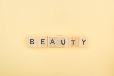 Photo pour Vue du dessus de lettrage beauté en cubes de bois sur fond jaune - image libre de droit