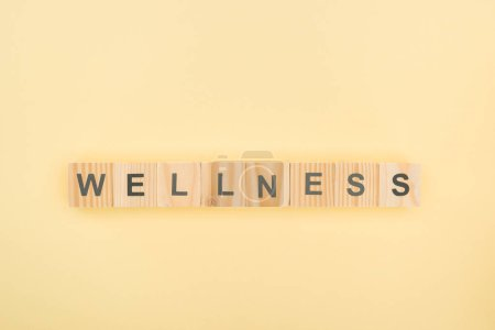 Photo for Top view of wellness lettering made of wooden cubes on yellow background - Royalty Free Image
